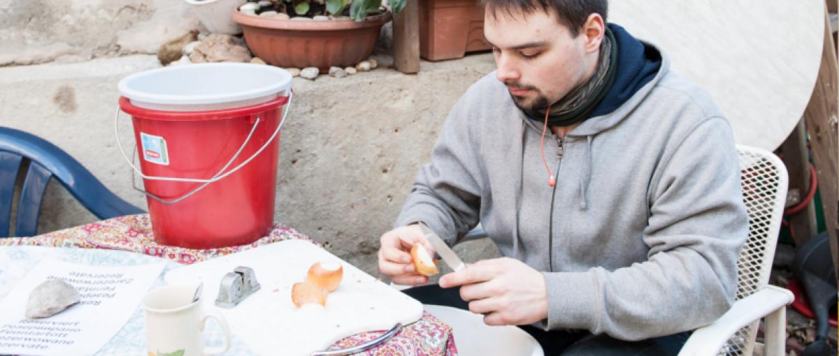 Ein Man sitzt bei einem Tisch und schält Zwiebel