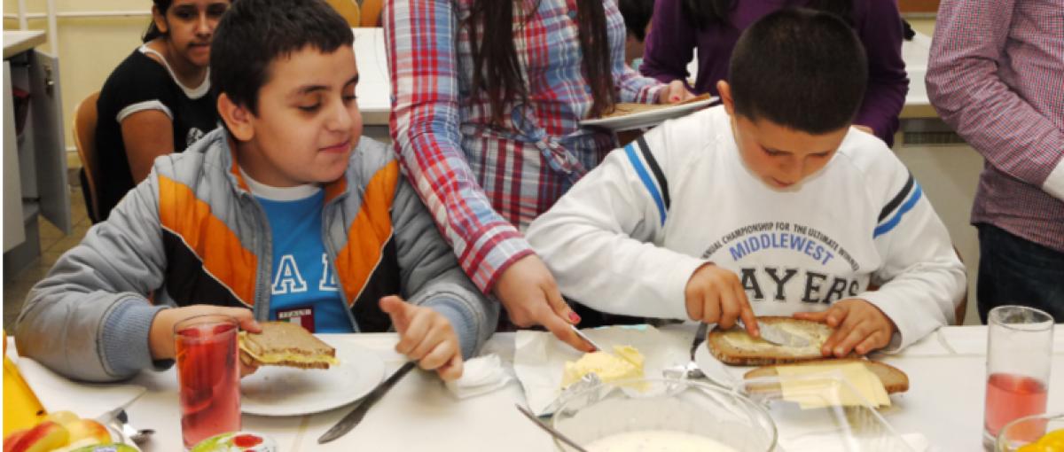 Zwei Buben sitzen in einer Schulklasse und bestreichen Jausenbrote mit Butter