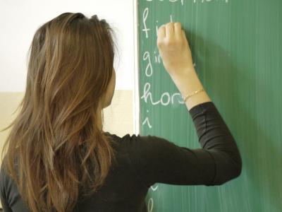 junge Frau schreibt an der Schultafel