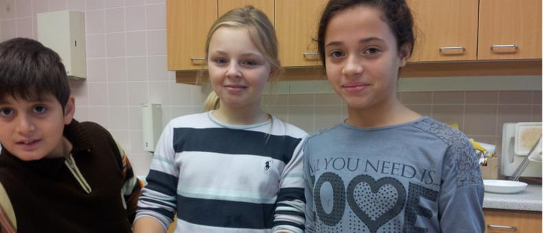 Zwei Mädchen blicken in die Kamera und stehen bei einer Anrichte, um Brote zu streichen